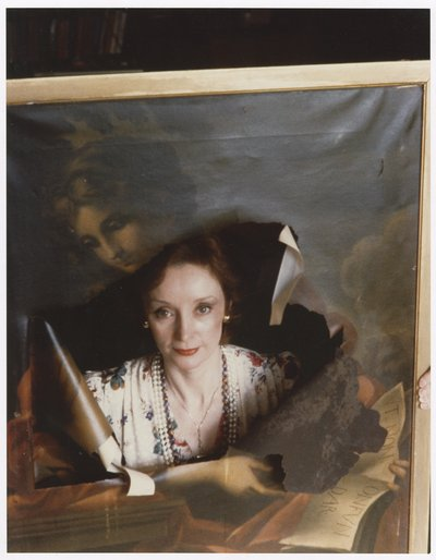 Woman looking through hole in a framed portrait of another woman