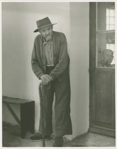 The photo shows a standing man with a cane and another man's face through a window