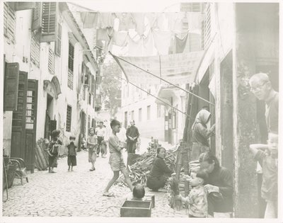 People in a cobblestone street between buildings with laundry hanging overhead