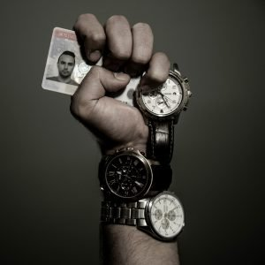 A composite photograph showing a clenched fist holding a blurred driver's license with three watches around the hand, wrist and forearm.
